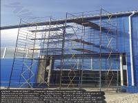 Общитие панелями производственного цеха посредством строительной вышки тура гигант